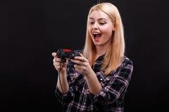Junges glückliches Mädchen spielt faszinierend mit einer Spielauflage und emotional sich freuen Auf einem schwarzen Hintergrund stockfoto