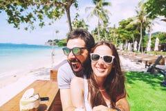 Junges glückliches Paar auf Flitterwochenferien unterhalten auf tropischem Strandhintergrund im Café Errichten Sie lustige Gesich lizenzfreie stockfotos