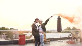 Junges glückliches Paar, das auf das Dach mit gelber Rauchbombe durch modernes Gebäude bei dem Sonnenuntergang geht outdoor Konze stock video