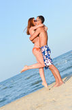 Junges glückliches Paar, das auf der Umfassung des sandigen Strandes küsst Stockfotografie