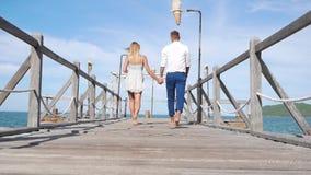 Junges glückliches Paar, das auf einen hölzernen Pier auf dem Hintergrund des blauen Himmels geht Romantisches Konzept HD, 1920x1 stock footage