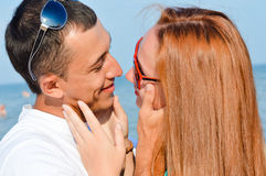 Junges glückliches Paar, das auf Seestrand umfasst Lizenzfreie Stockfotografie