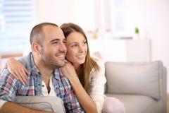Junges glückliches Paar, das auf Sofa fernsieht Lizenzfreie Stockfotos