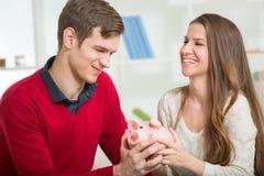 Junges glückliches Paar, das ein Sparschwein hält Lizenzfreie Stockfotografie
