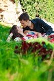 Junges glückliches Paar, das in einem Sommerpark flirtet Stockbild