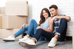 Junges glückliches Paar, das in ihr neues Haus umzieht lizenzfreie stockfotos