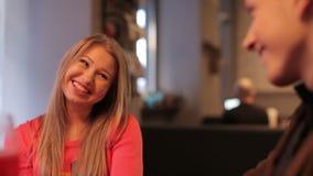 Junges glückliches Paar, das im Café, steadicam Schuss plaudert stock footage
