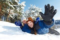 Junges glückliches Paar, das im Winter rodelt Stockbild