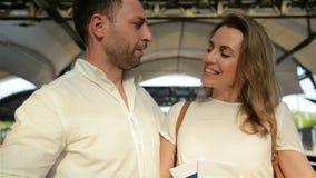 Junges glückliches Paar, das mit Gepäck auf der Rolltreppe zum Abfahrt-Bereich des Flughafens während ihres Sommers aufsteht stock video
