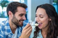 Junges glückliches Paar, das mit Kuchen sich einzieht lizenzfreie stockbilder
