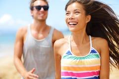 Junges glückliches Paar, das Spaß auf Strand habend lacht Stockbild