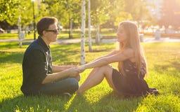 Junges glückliches Paar, das zusammen im Freien spricht - sitzend auf Gras lizenzfreies stockfoto