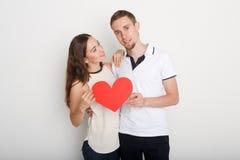 Junges glückliches Paar in der Liebe, die rotes Papierherz hält Stockbilder