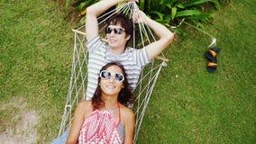 Junges glückliches Paar in der Sonnenbrille, die auf Hängematte sich entspannt Spitze der Ansicht Langsame Bewegung 1920x1080 stock video footage