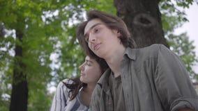 Junges glückliches Paar in der zufälligen Kleidung Zeit im Park zusammen verbringend, ein Datum habend Liebhaber, die auf der Ban stock footage