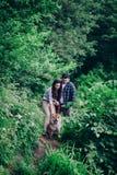 Junges glückliches Paar des Mannes und der Frau mit Hund am Rasen sitzen lizenzfreies stockbild
