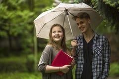 Junges glückliches Paar im Park unter einem Regenschirm, ein Mädchen hält ein rotes Buch in seinen Händen Lizenzfreie Stockfotos