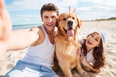 Junges glückliches Paar mit dem Hund, der ein selfie nimmt Stockfotografie