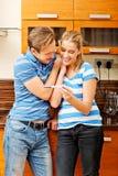 Junges glückliches Paar mit dem Schwangerschaftstest, der in der Küche steht lizenzfreies stockbild