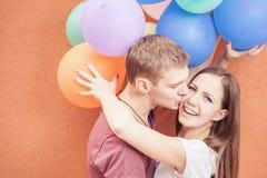 Junges glückliches Paar nahe dem orange Wandstand mit Ballonen Stockfoto