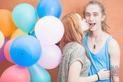 Junges glückliches Paar nahe dem orange Wandstand mit Ballonen Stockfotografie