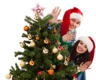 Junges glückliches Paar nahe einem Weihnachtsbaum. lizenzfreie stockfotos