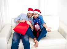 Junges glückliches Paar in Sankt-Hut auf dem Weihnachten, das Einkaufstaschen mit Geschenken hält Stockfotos