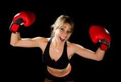Junges glückliches schönes Boxermädchen mit Boxhandschuhen bewaffnet im Siegeszeichen mit Sitz und gesundem Körper Stockbild