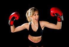 Junges glückliches schönes Boxermädchen mit Boxhandschuhen bewaffnet im Siegeszeichen mit Sitz und gesundem Körper Stockbilder