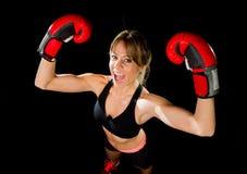 Junges glückliches schönes Boxermädchen mit Boxhandschuhen bewaffnet im Siegeszeichen mit Sitz und gesundem Körper Stockfoto