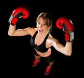 Junges glückliches schönes Boxermädchen mit Boxhandschuhen bewaffnet im Siegeszeichen mit Sitz und gesundem Körper Stockfotografie