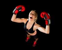 Junges glückliches schönes Boxermädchen mit Boxhandschuhen bewaffnet im Siegeszeichen mit Sitz und gesundem Körper Lizenzfreie Stockbilder