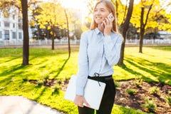 Junges glückliches schönes Mädchen, das in den Park mit einem Laptop geht und stockfotografie