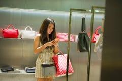 Junges glückliches und schönes asiatisches koreanisches Fraueneinkaufen und mit Handy am Luxustaschenshop, der um den Speicher in lizenzfreies stockfoto