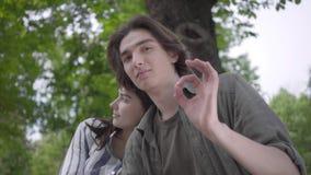 Junges gl?ckliches Paar in der zuf?lligen Kleidung Zeit im Park zusammen verbringend, ein Datum habend Liebhaber, die auf der Ban stock video footage