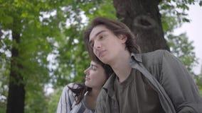 Junges gl?ckliches Paar in der zuf?lligen Kleidung Zeit im Park zusammen verbringend, ein Datum habend Liebhaber, die auf der Ban stock footage