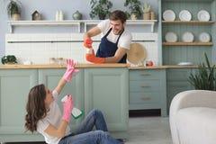 Junges gl?ckliches Paar hat Spa? beim Reinigung zu Hause tun stockbild
