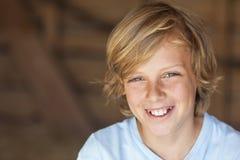 Junges glückliches blondes Jungen-Kinderlächeln Stockfoto
