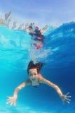 Junges glückliches lächelndes Kind, das unter Wasser im blauen Pool schwimmt Lizenzfreie Stockbilder