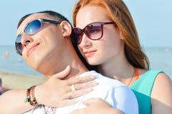 Junges glückliches Paar, das auf sandigem Strand sitzt und tragende Sonnenbrillen umfasst Stockfotografie