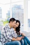 Junges glückliches Paar, das digitale Tablette betrachtet Stockbild