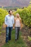 Junges glückliches Paar, das nebeneinander während Händchenhalten geht Lizenzfreies Stockfoto