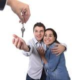 Junges glückliches Paar, das neuen Schlüsselwohnsitz des Hauses im Konzept des wirklichen Zustandes empfängt Stockfotografie