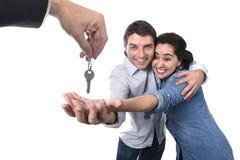 Junges glückliches Paar, das neuen Schlüsselwohnsitz des Hauses im Konzept des wirklichen Zustandes empfängt Stockfoto