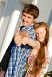 Junges glückliches Paar, das sich Daumen zeigt Stockfotos