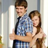 Junges glückliches Paar, das sich Daumen zeigt Stockbilder