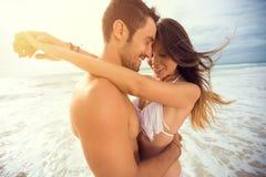 Junges glückliches Paar mit Herzen des abgehobenen Betrages auf tropischem Strand Lizenzfreies Stockbild
