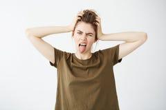 Junges grobes Mädchen, welches die Zunge blinzelt zeigt, die Kamera betrachtend, die Hauptweißen übermäßighintergrund hält Lizenzfreies Stockbild
