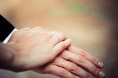 Junges Händchenhalten des verheirateten Paars, Zeremoniehochzeitstag Lizenzfreie Stockfotografie