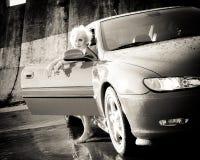 Junges hübsches Frauenverlassen einen Sportwagen Stockbilder
